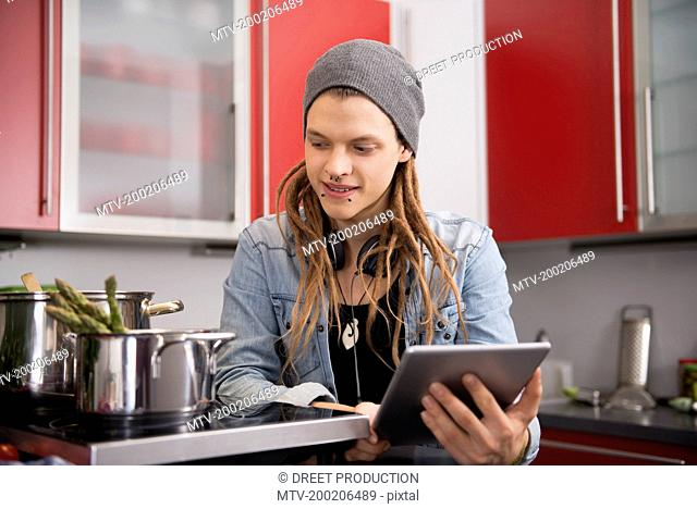 Young man looking at recipe on digital tablet, Munich, Bavaria, Germany