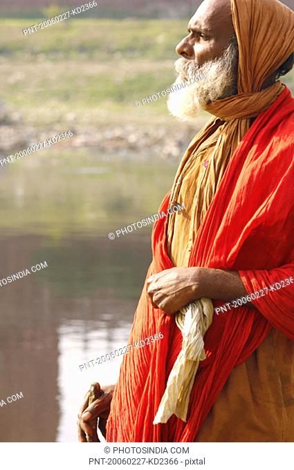 Side profile of a priest standing near the river