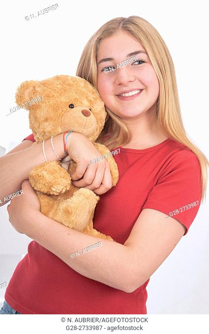 Portrait of happy blond teenage girl cuddling her teddy bear at home