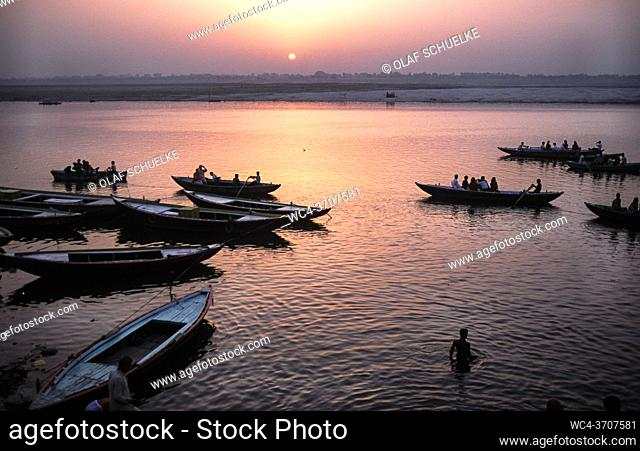Varanasi, Uttar Pradesh, India, Asia - Daybreak with sunrise over wooden rowboats at a ghat on the bank along the holy Ganges River