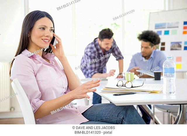 Businesswoman talking on cell phone in conference room