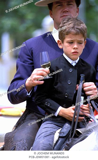 horseman and his son with glass of sherry at the feria del caballo
