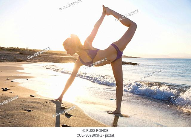 Young woman on beach, in yoga position