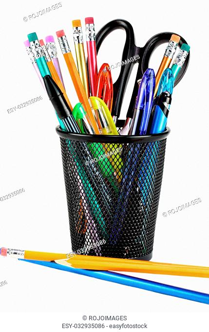 Black metal pencil cup filled with colorful pencils, pens and a pair of scissors. On white with copy space