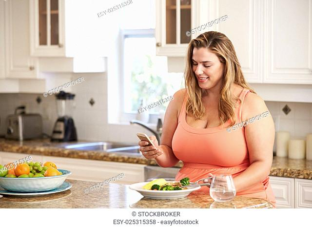 Overweight Woman Eating Healthy Meal And Using Mobile Phone