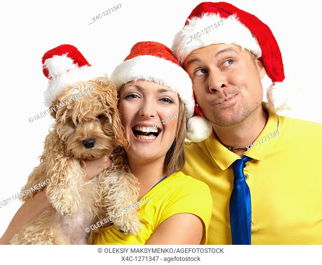 Portrait of a happy young man and a woman with a Cockapoo dog in her hands wearing red Christmas hats
