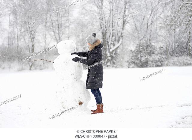 Germany, woman building snowman