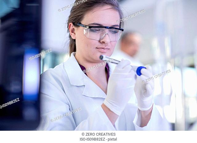 Laboratory worker writing details on test tube