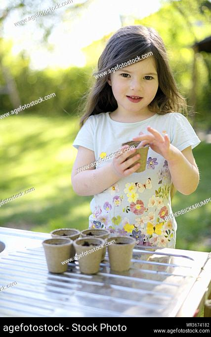 Cute girl planting seeds in small pots on table at yard