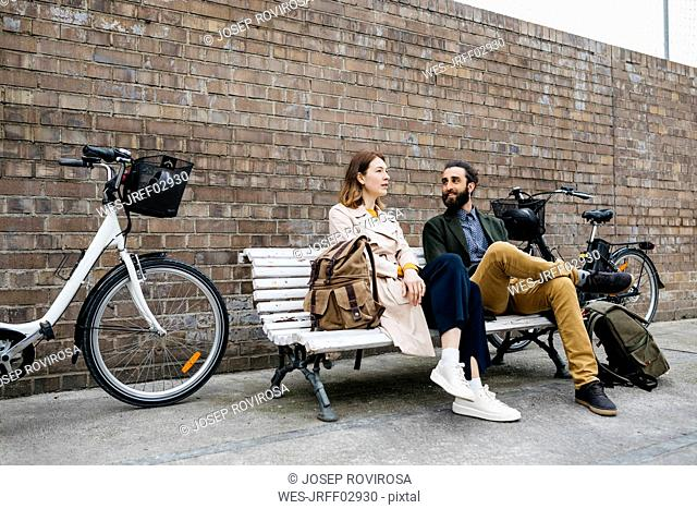 Couple sitting on a bench next to e-bikes talking