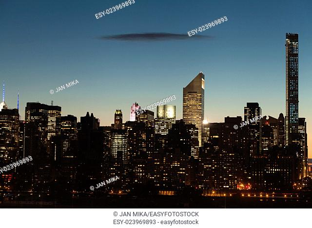 Midtown Manhattan cityscape with clear sky and one dark flat cloud during twilight in New York City