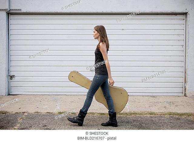 Caucasian woman carrying guitar case on sidewalk