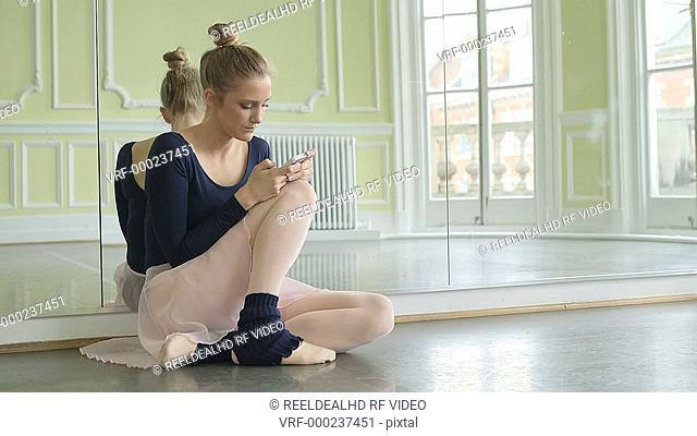 Female Ballet Dancer crouches in front of the studio mirror and uses her smartphone