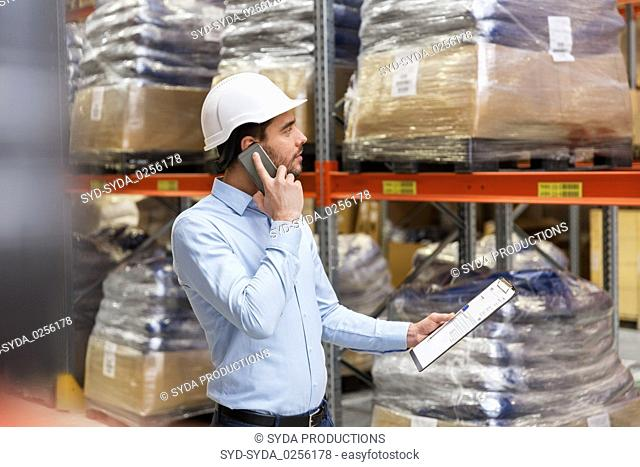businessman calling on smartphone at warehouse