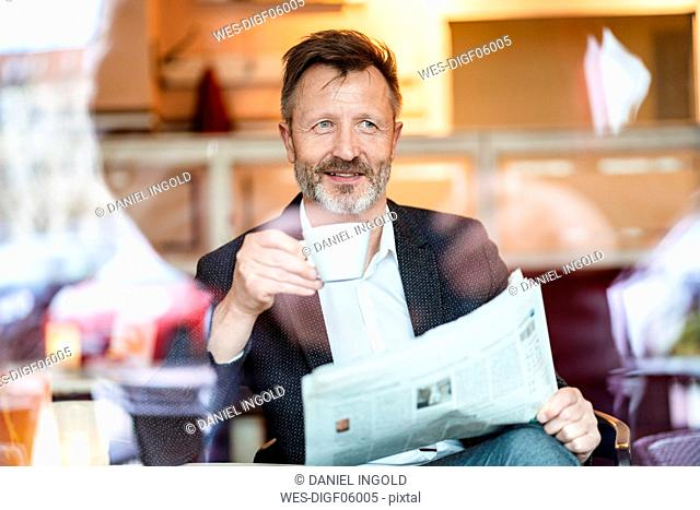 Portrait of smiling mature businessman with newspaper sitting in a coffee shop drinking coffee