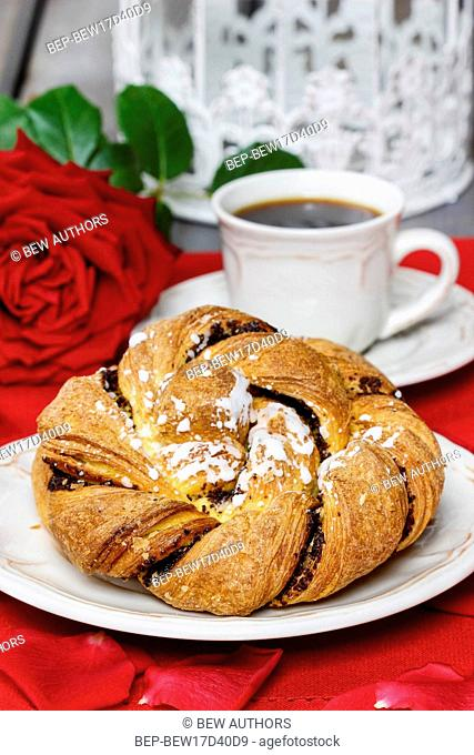 Festive braided bread on white plate. Rose petals around, bouquet of roses in the background