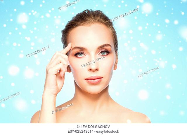 beauty, people and winter concept - beautiful young woman showing her forehead over blue background and snow