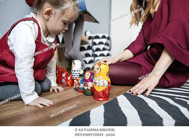 Mother playing with daughter in children's room at home