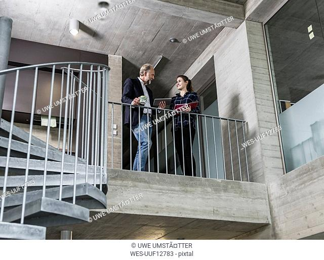 Smiling mature businessman and young woman talking in staircase