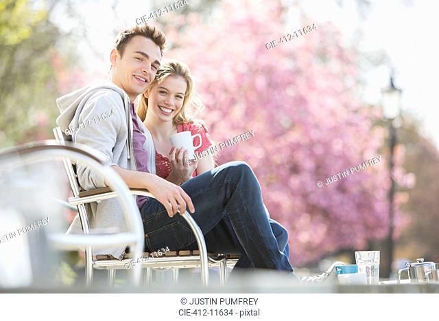 Couple having coffee on park bench