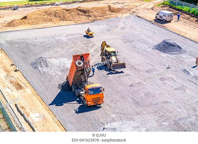 The dump truck unloads the gravel on the construction site of the school stadium