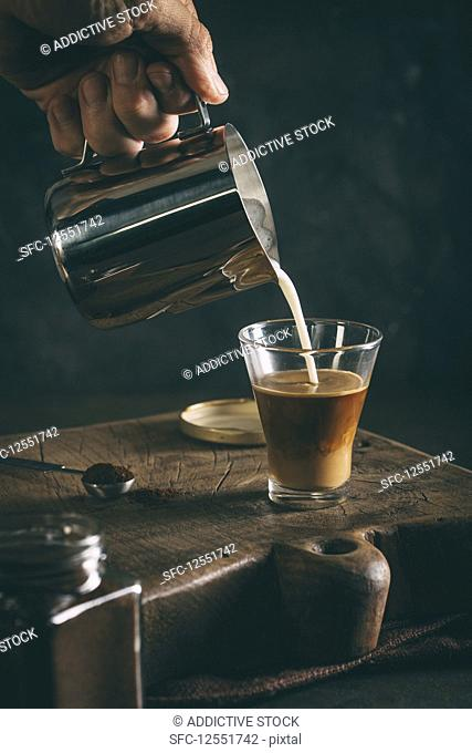 Pouring hot milk into a glass on dark background