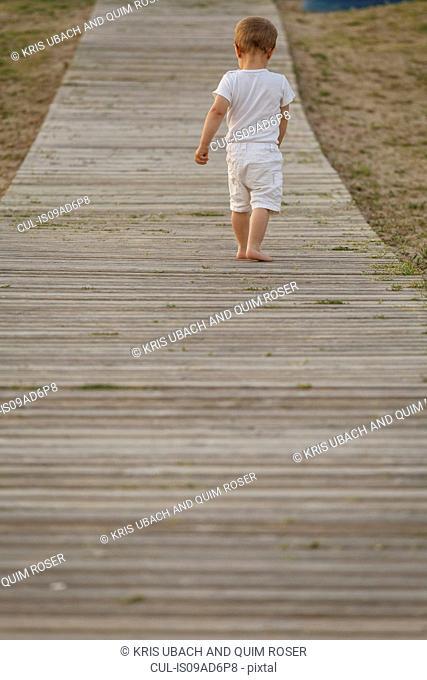 Rear view of toddler walking along boardwalk