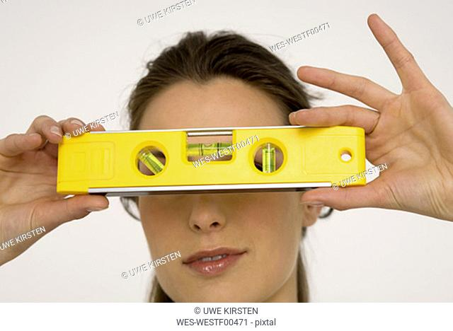 Young woman holding spirit level, close-up