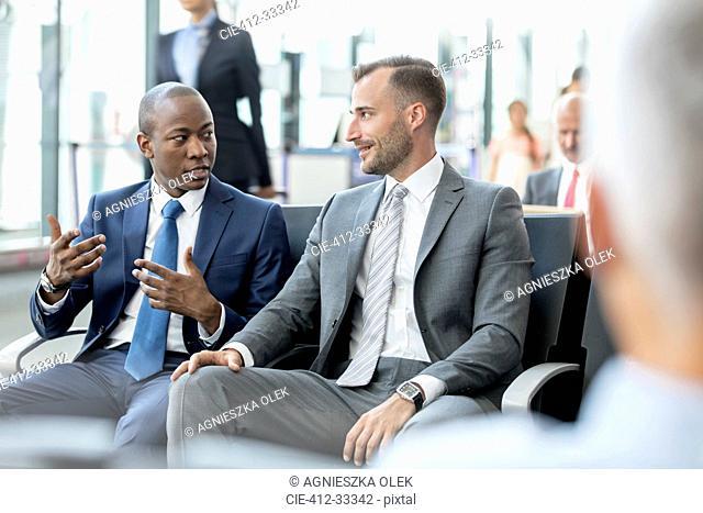 Businessmen talking in airport departure area