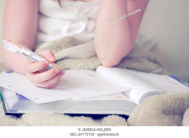 Mid section of girl (10-12) doing homework