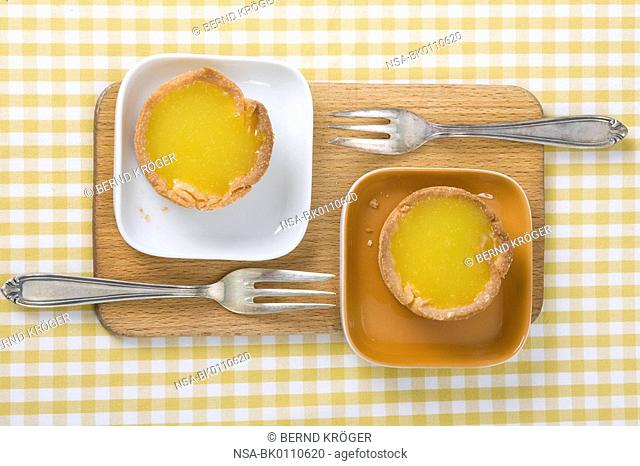 Two small orange tarts on small bowls