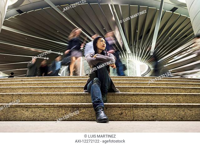 A young woman sitting on steps with a modern building and pedestrians in the background, Kowloon; Hong Kong, China