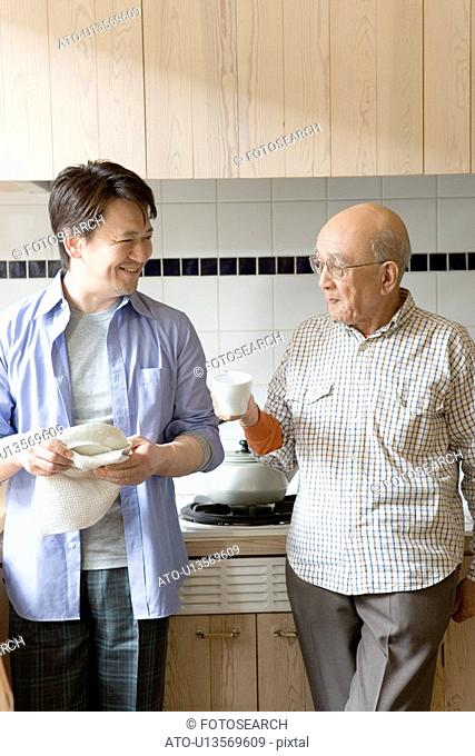 Mid Adult Man and Senior Adult Man Talking in Kitchen, Holding Mug Cup, Front View