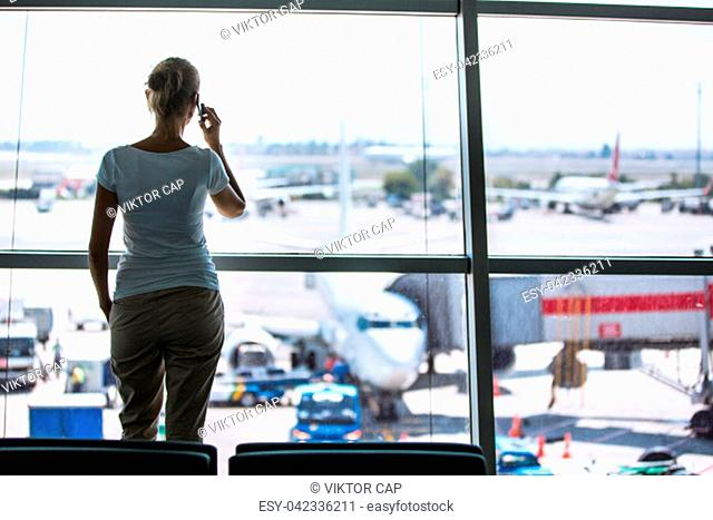 Pretty, young woman waiting at a gate area of a modern airport for the boarding call - making some calls(color toned image; shallow DOF)