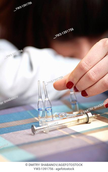 women and drags syringe on the table