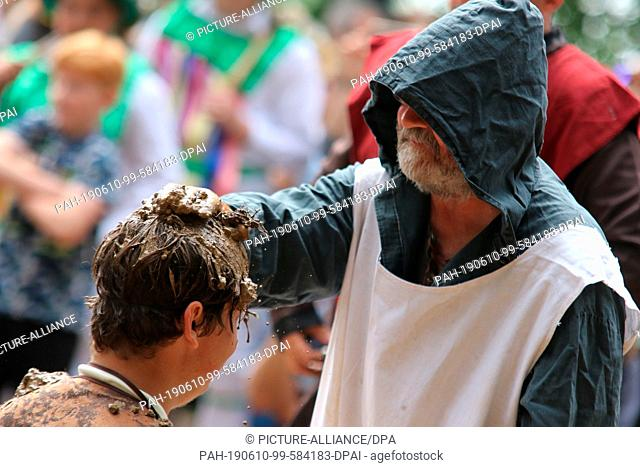 10 June 2019, Saxony-Anhalt, Hergisdorf: At the traditional dirty pig festival, a man sits in a mud dump, while a man standing in front of him smears mud on his...