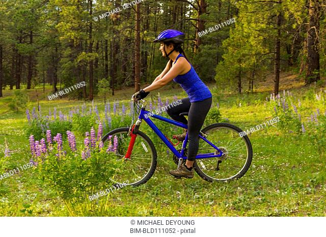 Chinese woman riding mountain bike in meadow