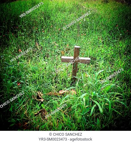 A cross surrounded by grass in a cemetery in Chiapas, Mexico