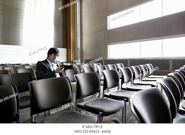 Man texting with cell phone in empty auditorium