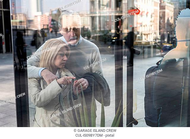 Senior couple window shopping in city