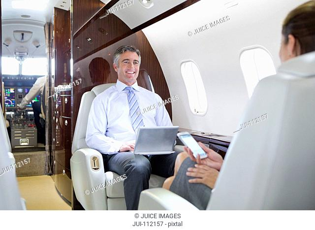 Businesswoman on phone and smiling Businessman with digital tablet having meeting on private jet