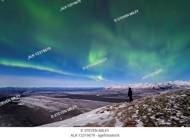 A man observes the aurora borealis from the top of Donnelly Dome south of Fort Greely and Delta Junction, Interior Alaska, USA