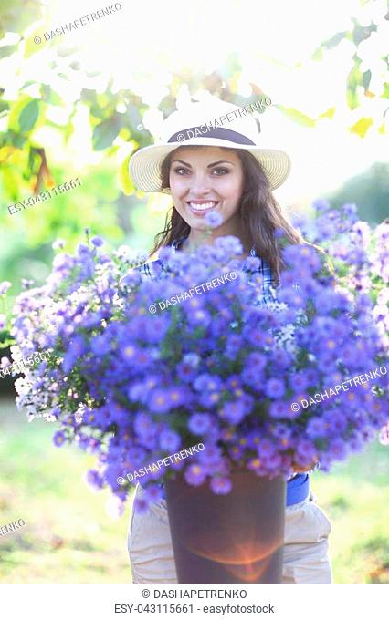 Happy woman florist with bouquet of flowers bucket outdoors