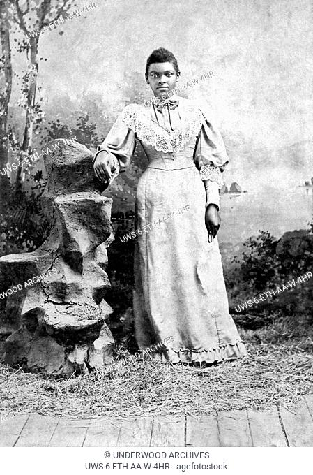 Jackson, Mississippi: c. 1890.A studio portrait of a young African American woman with her arm resting on a carved stump