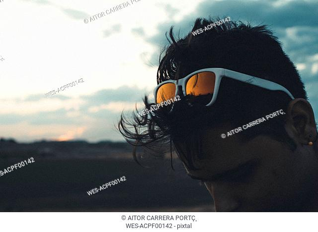 Young man with sunglasses looking down, silhouette