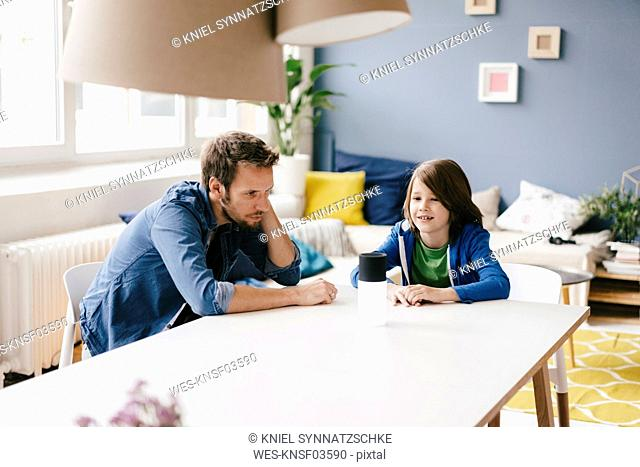 Father and son looking at innovative item on table at home