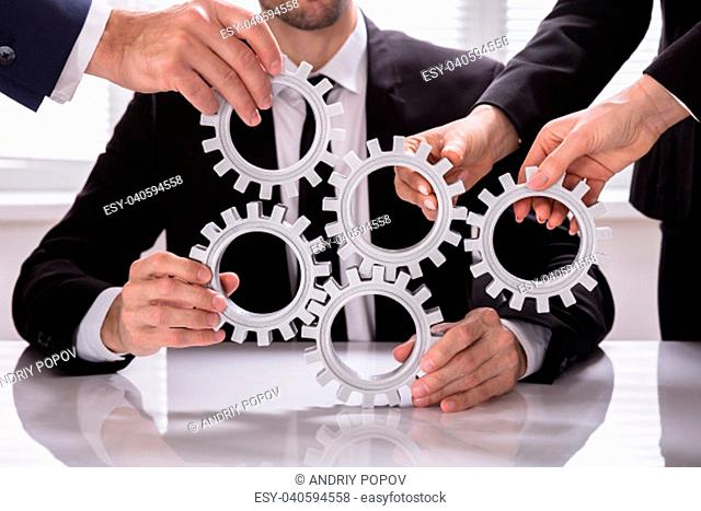 Group Of Businesspeople Stacking Gears On Desk In Office