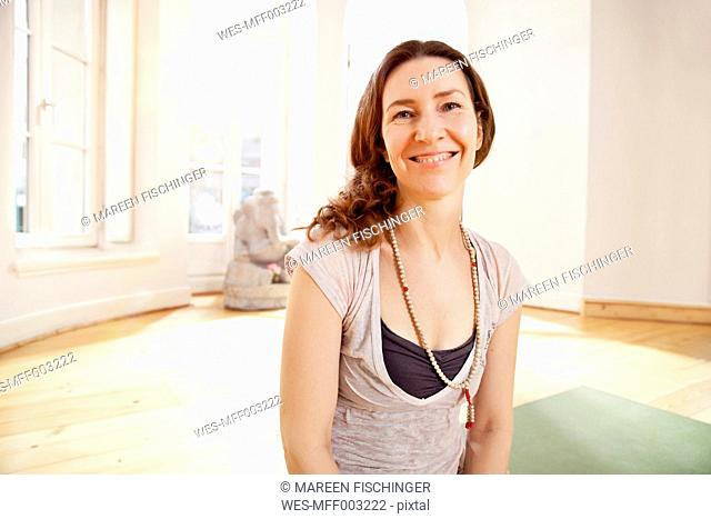 Portrait of smiling woman in sunny yoga studio