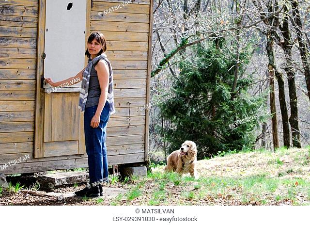 Woman standing close to open a door when a dog is watching