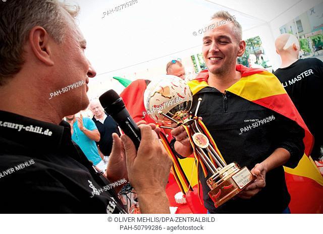 "Winner Stephan Kuehne, who competed for Macedonia, gives an interview after the world spicy food eating contest at the """"Curry & Chili"""" snack shop in Berlin"